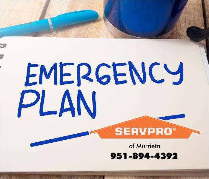 """Emergency plan"" is seen written on a white notepad in blue ink."