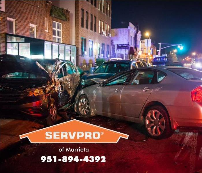 A silver sedan has crashed into a car parked car, pushing the parked car into the side a large brick building, damaging the b